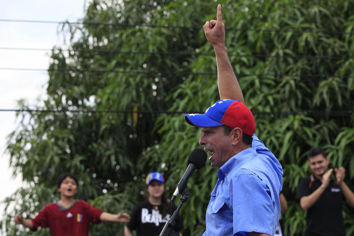 Opposition presidential candidate Henrique Capriles speaks to supporters at a campaign rally in Puerto Cabello, Venezuela, Wednesday, Sept. 12, 2012. Violence broke out before the opposition campaign event got started, between supporters of Capriles and s