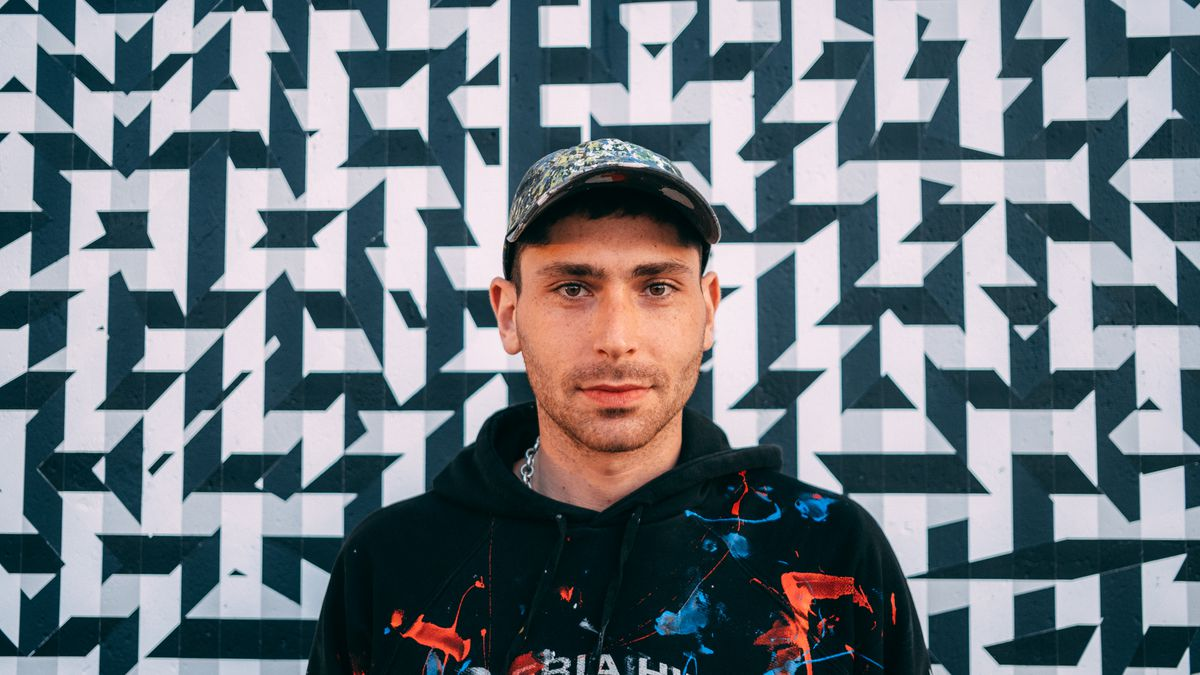 """Daniel Shoykhet in front of his mural titled """"KVTNO9"""" at Hubbard Street and Milwaukee Avenue. He used shapes and crossing patterns to give an illusion of motion."""