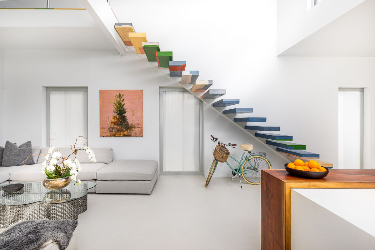 A rainbow floating staircase rises on one wall, with a gray couch in a living room on the left.