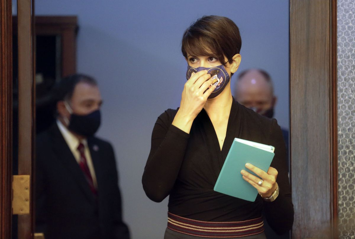 State epidemiologist Dr. Angela Dunn adjusts her face mask before a COVID-19 briefing at the Capitol in Salt Lake City on Thursday, July 16, 2020. Gov. Gary Herbert is behind her.