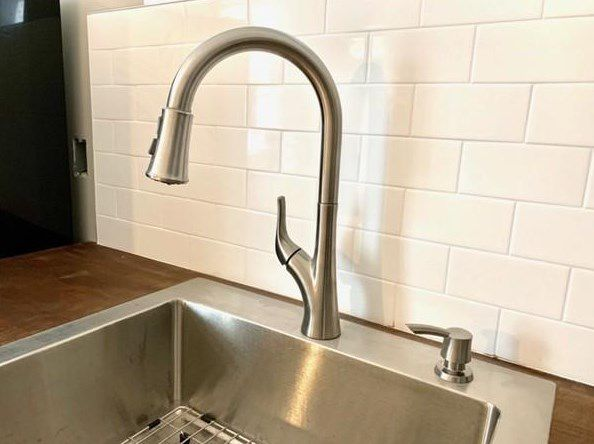 Closeup of the faucet of a new kitchen sink.