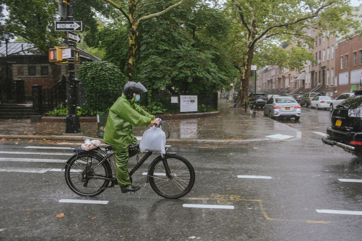 A delivery worker in a green rain poncho bikes on the street through a downpour.