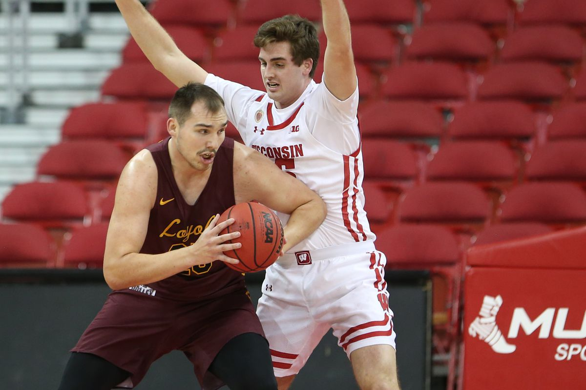 Loyola Ramblers center Cameron Krutwig works the ball past Wisconsin Badgers forward Nate Reuvers during the first half at the Kohl Center.