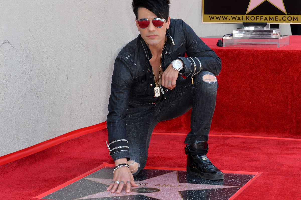 Criss Angel kneels next to his star on the Hollywood Walk of Fame in 2017.