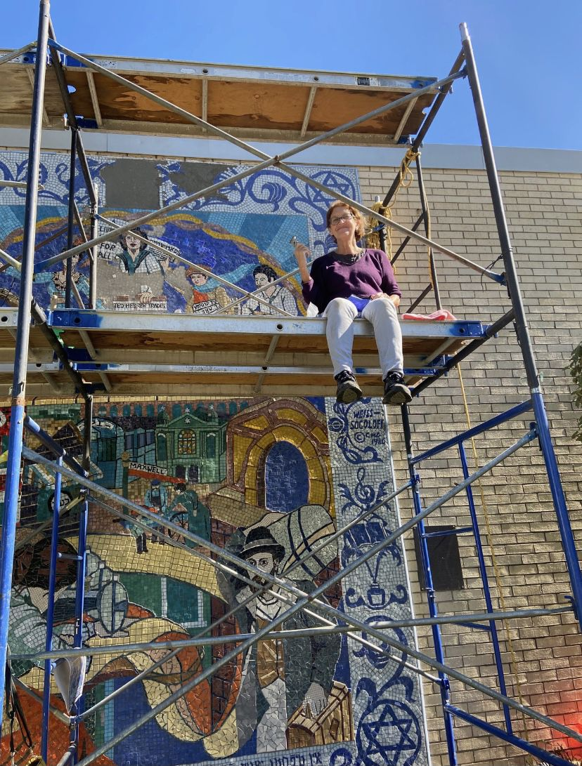 """Artist Cynthia Weiss sits on the scaffolding used to repair the top part of the """"Fabric of Our Lives"""" mosaic at the Bernard Horwich Jewish Community Center."""