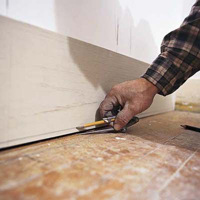 Man Uses Compass to Ensure Tight Fit Of Baseboard Along Bottom Of Floor