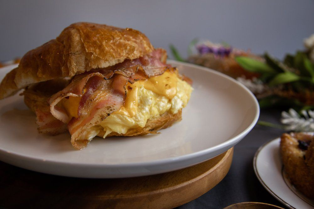 A breakfast croissant sandwich served with lots of soft scrambled eggs and lightly cooked bacon.
