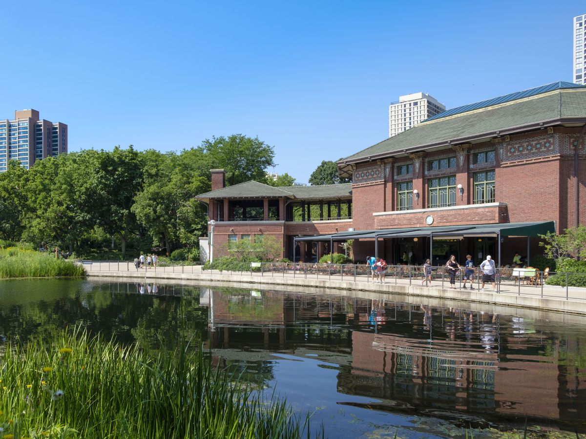 A brick Prairie style building with an outdoor patio next to a lagoon.