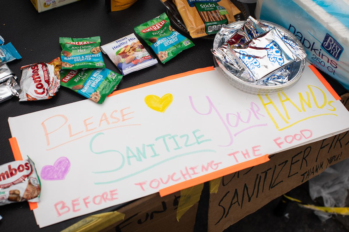 "Snacks are spread out on a table, with a colorful handmade sign that reads ""Please sanitize your hands before touching the food"""