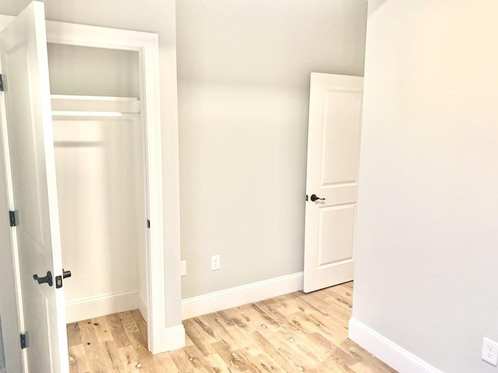 A squat hallway with a door opened on an empty closet.