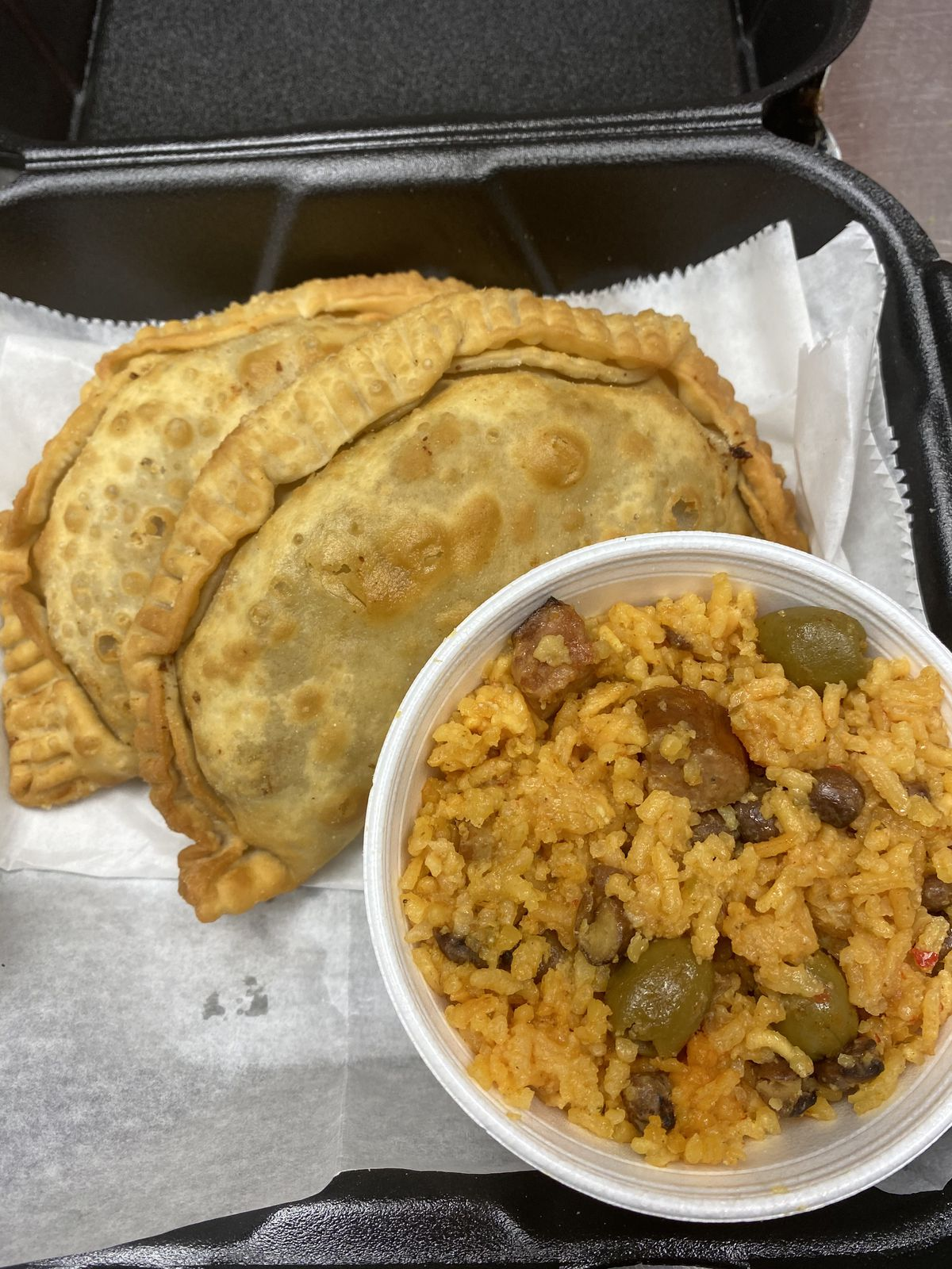 Two empanadas and a cup of orange rice in a styrofoam cup.