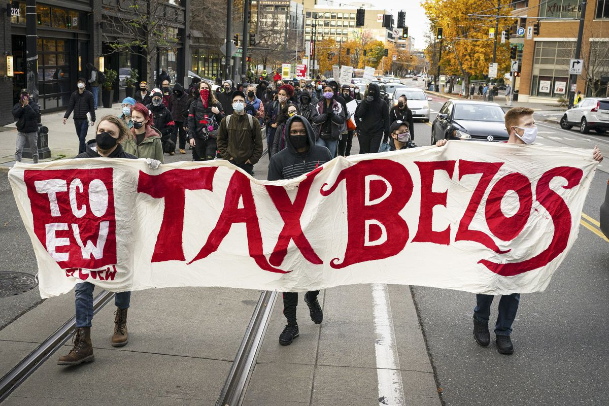 """Demonstrators march in front of Amazon's headquarters in November 2020 holding a sign saying """"Tax Bezos."""""""