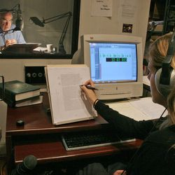 """Director Johanna Parker, right, makes notes on her copy of text as she directs the recording of narrator George Guidall, seated inside a recording booth, left, during a recording session for an audiobook of Vince Flynn's """"Consent to Kill"""" at Recorded Books Productions in New York on Aug. 29, 2005."""