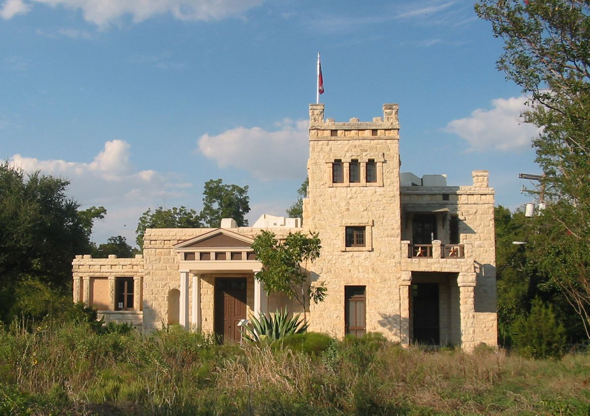 A tan-colored stone building features a covered entrance with white columns and a tower with a flag on top.