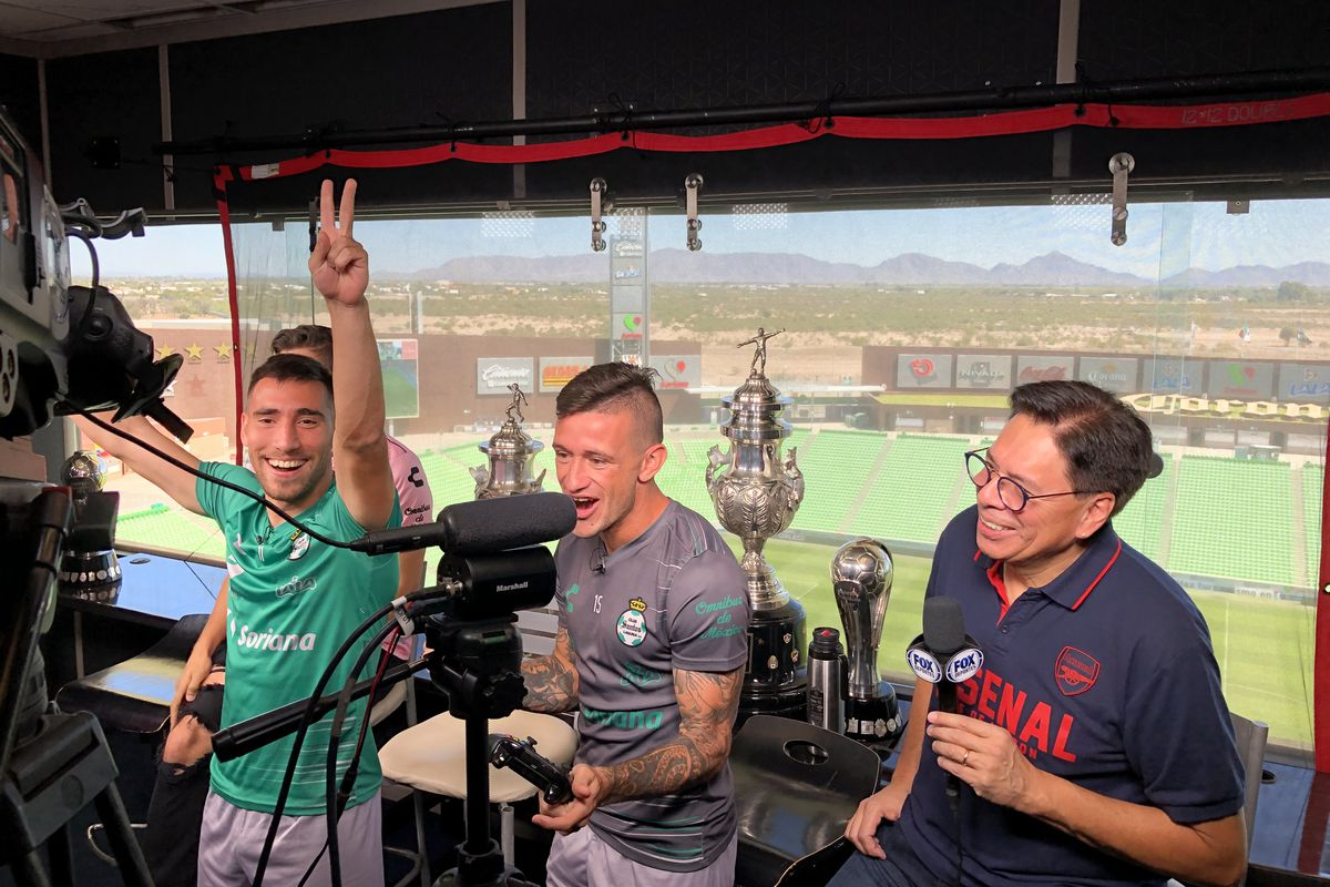Fernando Gorriarán (L) and Brian Lozano of Santos Laguna celebrate a goal in a FIFA tournament against FOX Deportes talent to raise awareness for Play Pink, a breast cancer awareness initiative.