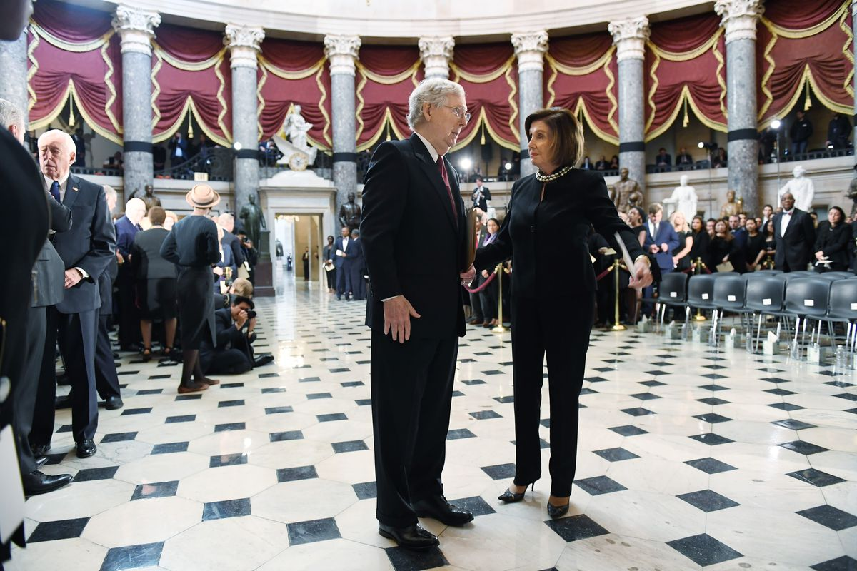 Senate Majority Leader Mitch McConnell (R-KY) and Speaker of the House Nancy Pelosi stand and talk to one another in the National Statuary Hall of the US Capitol building.
