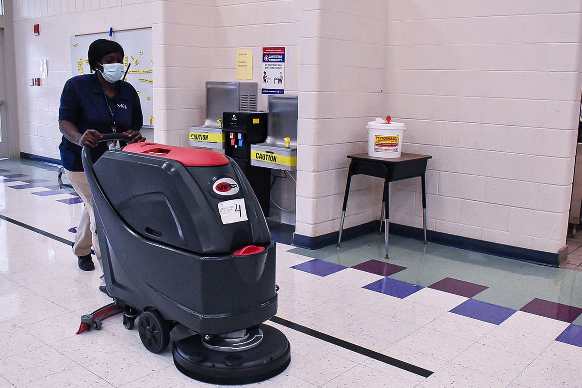 A Shelby County Schools worker, wearing a blue polo shirt and a blue face shield, pushes a floor pad down a tiled hallway.