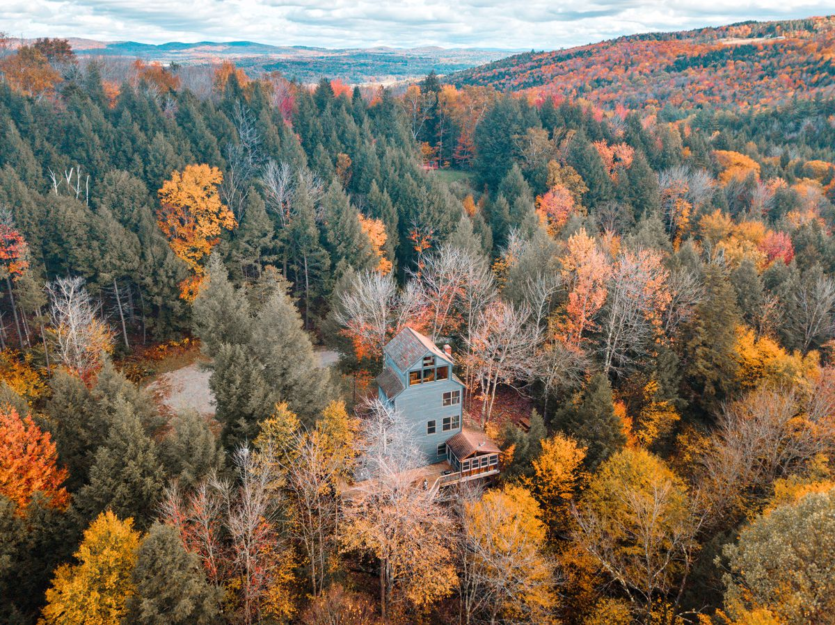 An aerial view of a five-story gray house surrounded by autumn trees in yellows, reds, and orange, with green pine trees sprinkled in.