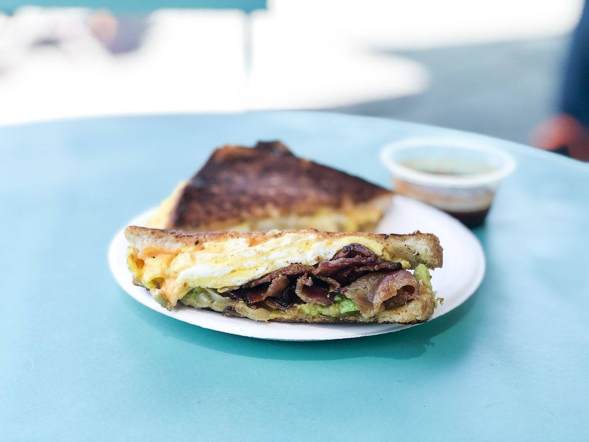 A toasted breakfast sandwich with scrambled eggs and lots of bacon on a blue table.