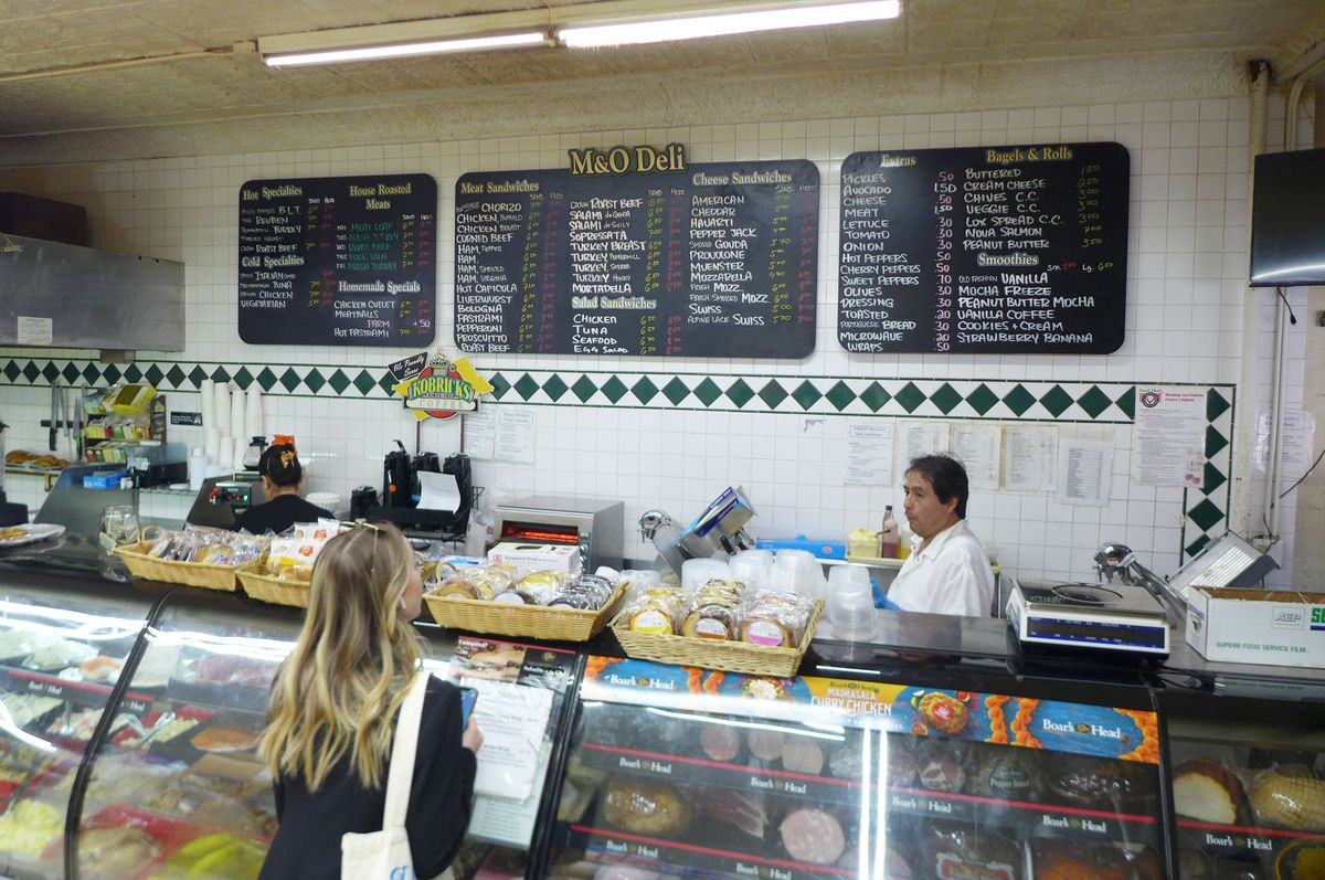 A deli counter with a giant menu hanging overhead.