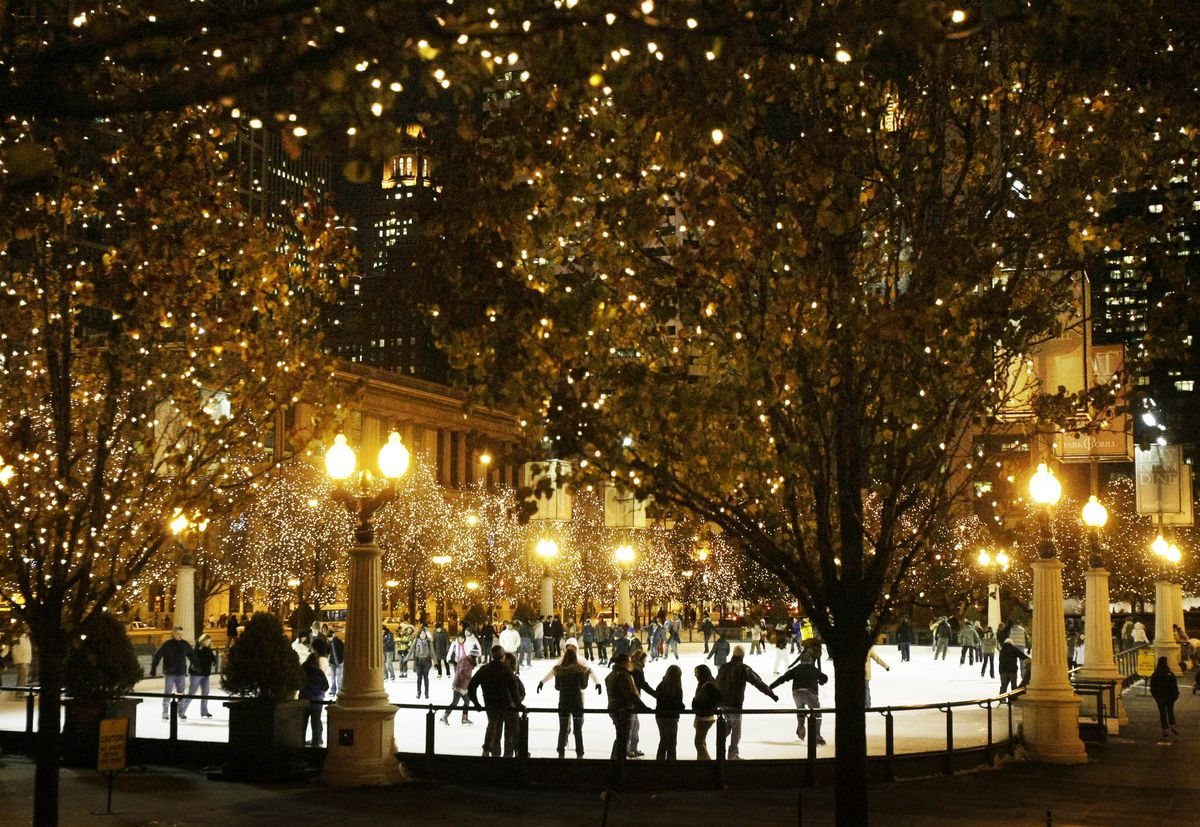 An ice-skating rink with lighted trees, street lamps and light snow fall.