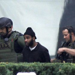 Pittsburgh police and SWAT members escort a suspect, center left,  from a hostage-taking on the 16th floor at Three Gateway Center to a police van on  Friday, Sept. 21, 2012, in Pittsburgh. Klein Michael Thaxton, 22, surrendered just before 2 p.m., and the man he took hostage was unhurt, Police Chief Nathan Harper said.