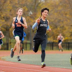 A Mather runner gives a smile and a peace sign as he runs in the meet at River Park.