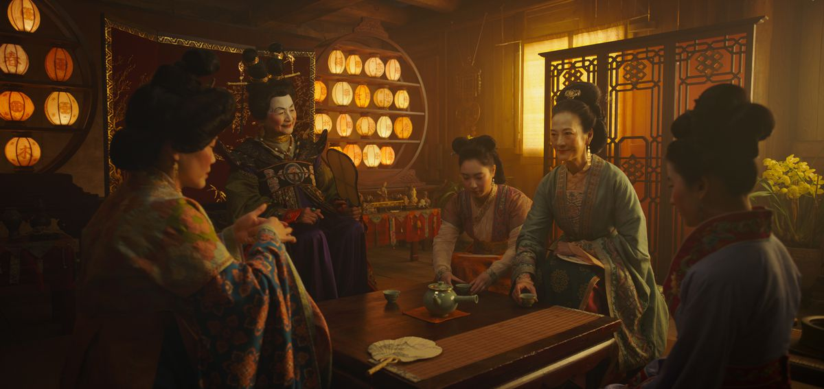 a group of women sit around a table in mulan