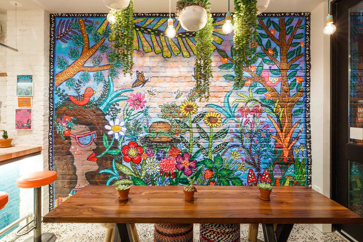 Plants hang near a mural depicting flowers and burgers at Lekka Burger; orange bar stools appear on the left side of the frame