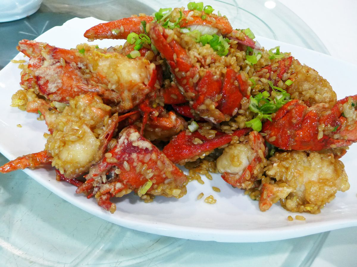 A heap of red shelled lobsters dotted with grains of sticky rice.
