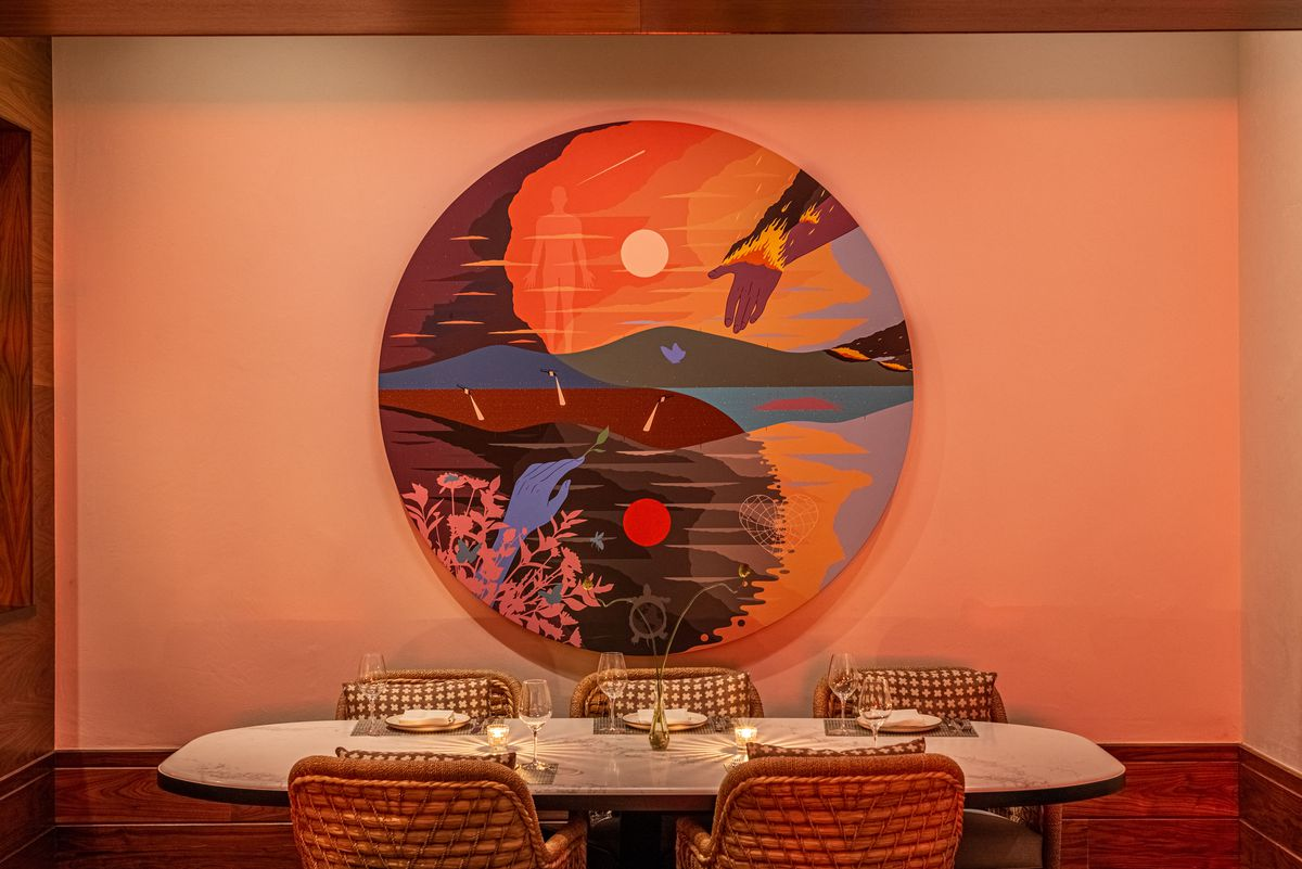 A dim red wall showing a round artist mural and six-top table at front.