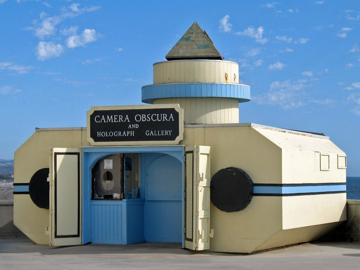 A small building on a beach with a sign that has the words: Camera Obscura and Holograph Gallery.