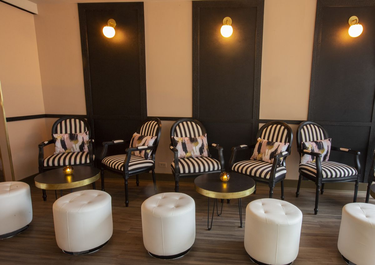A wall with big, thick black-and-white stripes with similarly striped chairs and round white stools.