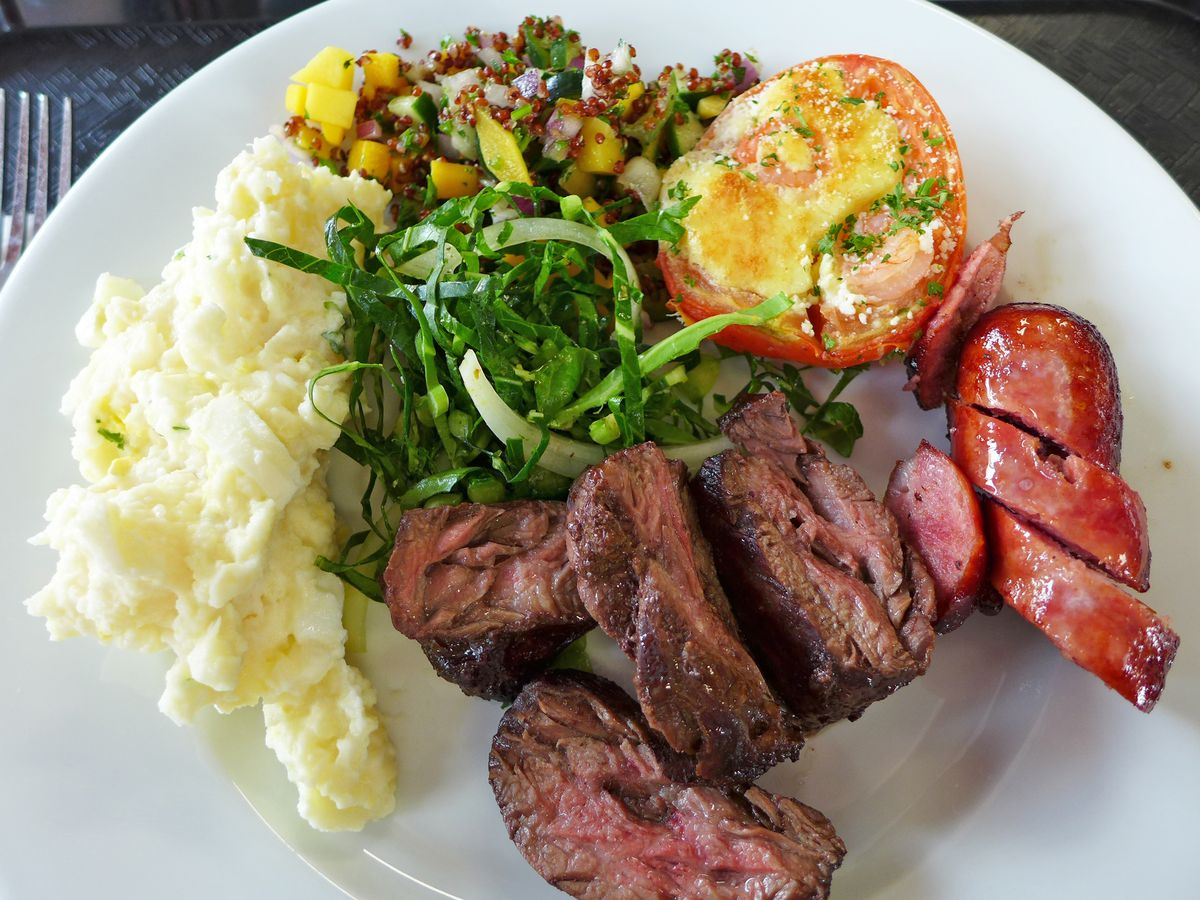 A plate from a Brazilian buffet with grilled steak, sausage, mashed potatoes, shredded kale, and a stuffed and grilled tomato