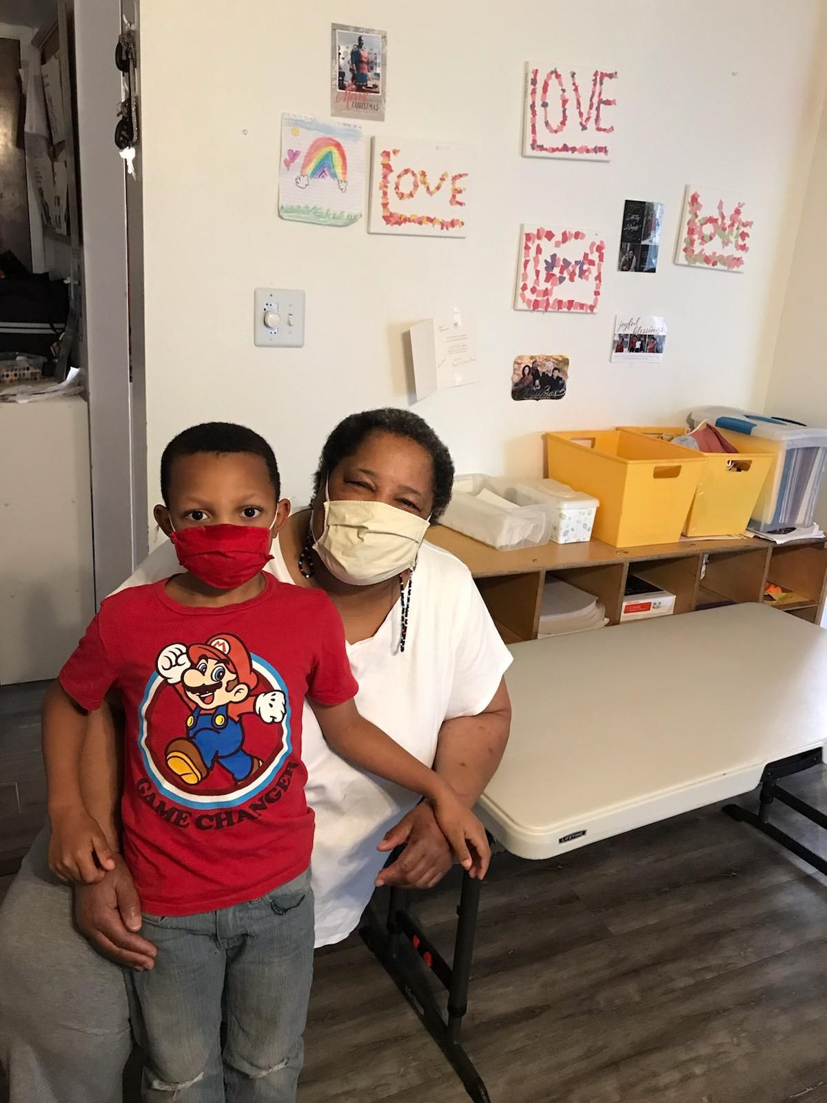 """A child care provider with a child, both wearing masks, beneath signs that say """"Love."""""""