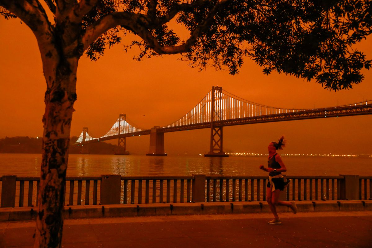 The Bay Bridge across San Francisco Bay at twilight, with the sky orange with smoke.