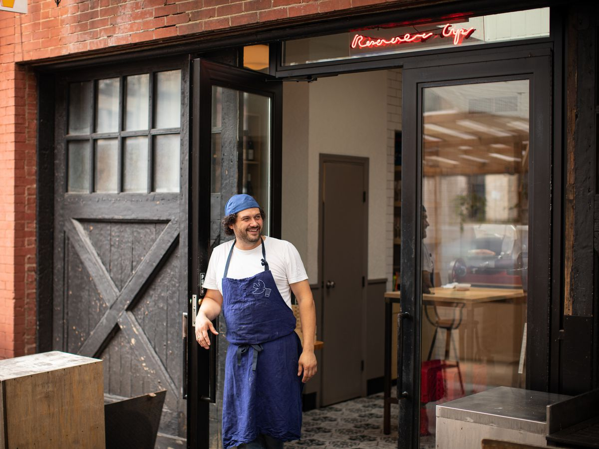 Daniel Eddy, the owner of Winner and Runner Up, stands in front of his second restaurant in a blue apron and backwards hat.