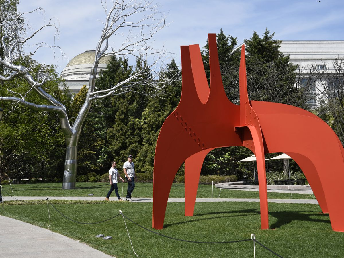 A portion of the National Gallery of Art Sculpture Garden. There is a large metal abstract sculpture on a grassy lawn.