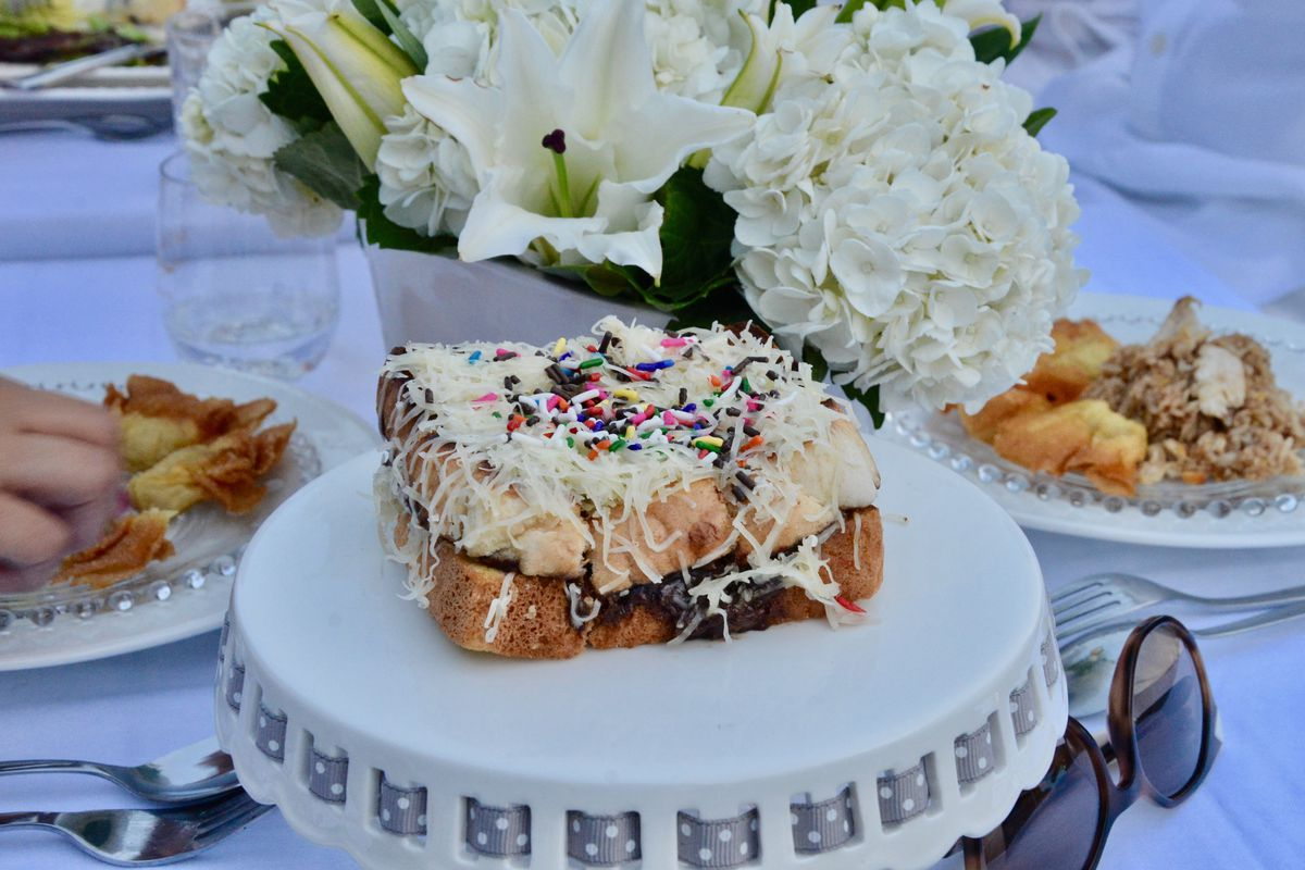 sandwich with chocolate spread, shredded cheese, and rainbow sprinkles in front of vase of flowers