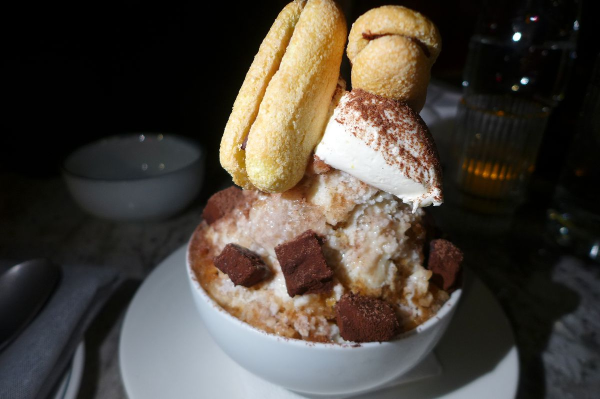 A heap of ice in a white bowl with brown powder and two cookies on top.