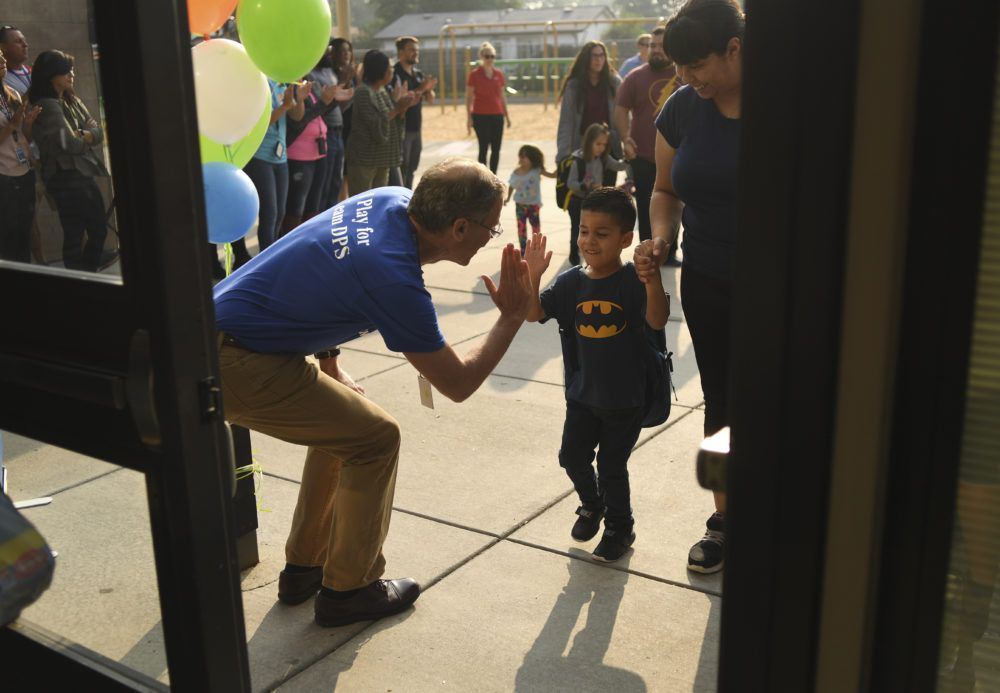 Boasberg high-fives Damian Lopez, 4, as he arrives in August for the first day of school at Escalante-Biggs Academy, a district school that serves students in preschool and kindergarten. The high-five was Boasberg's signature greeting.