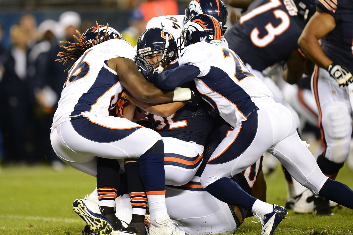 Aug 09, 2012; Chicago, IL, USA;  Denver Broncos linebacker Nate Irving (56) and defensive back Champ Bailey (24) tackle Chicago Bears running back Kahlil Bell (32) during the second quarter at Soldier Field. Mandatory Credit: Mike DiNovo-US PRESSWIRE