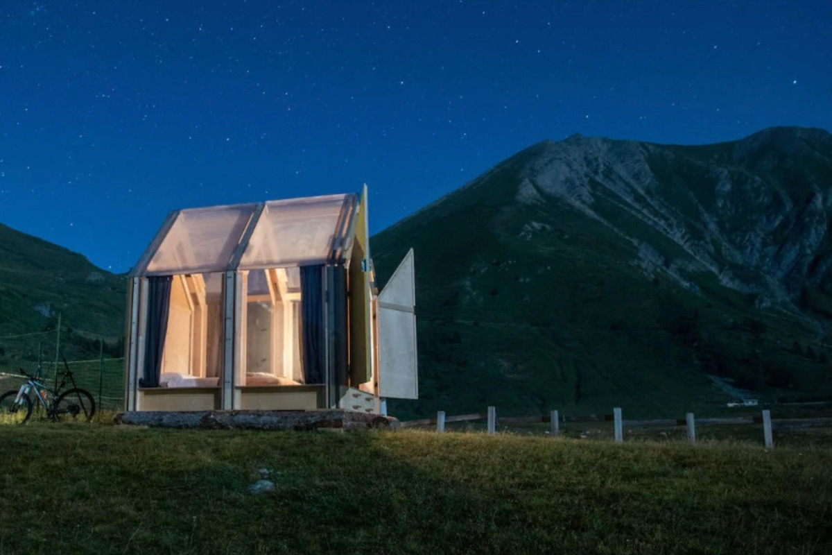Transparent gabled cabin in field at night with a mountain in the back.
