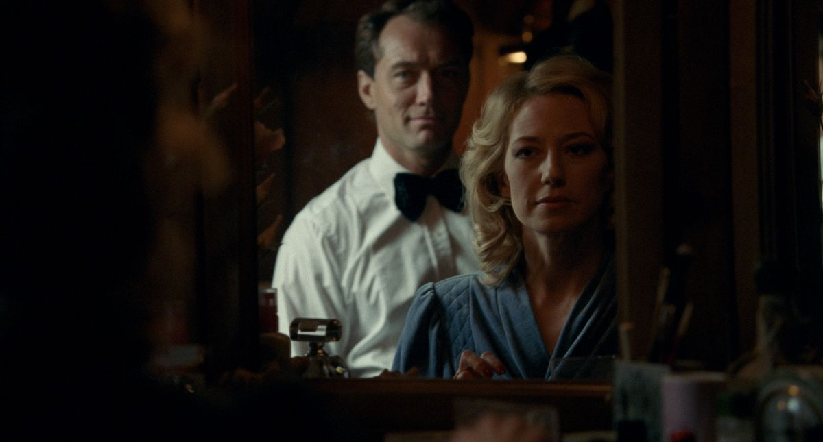 Jude Law and Carrie Coon look in a mirror while dressing up in fancy clothes in THe Nest