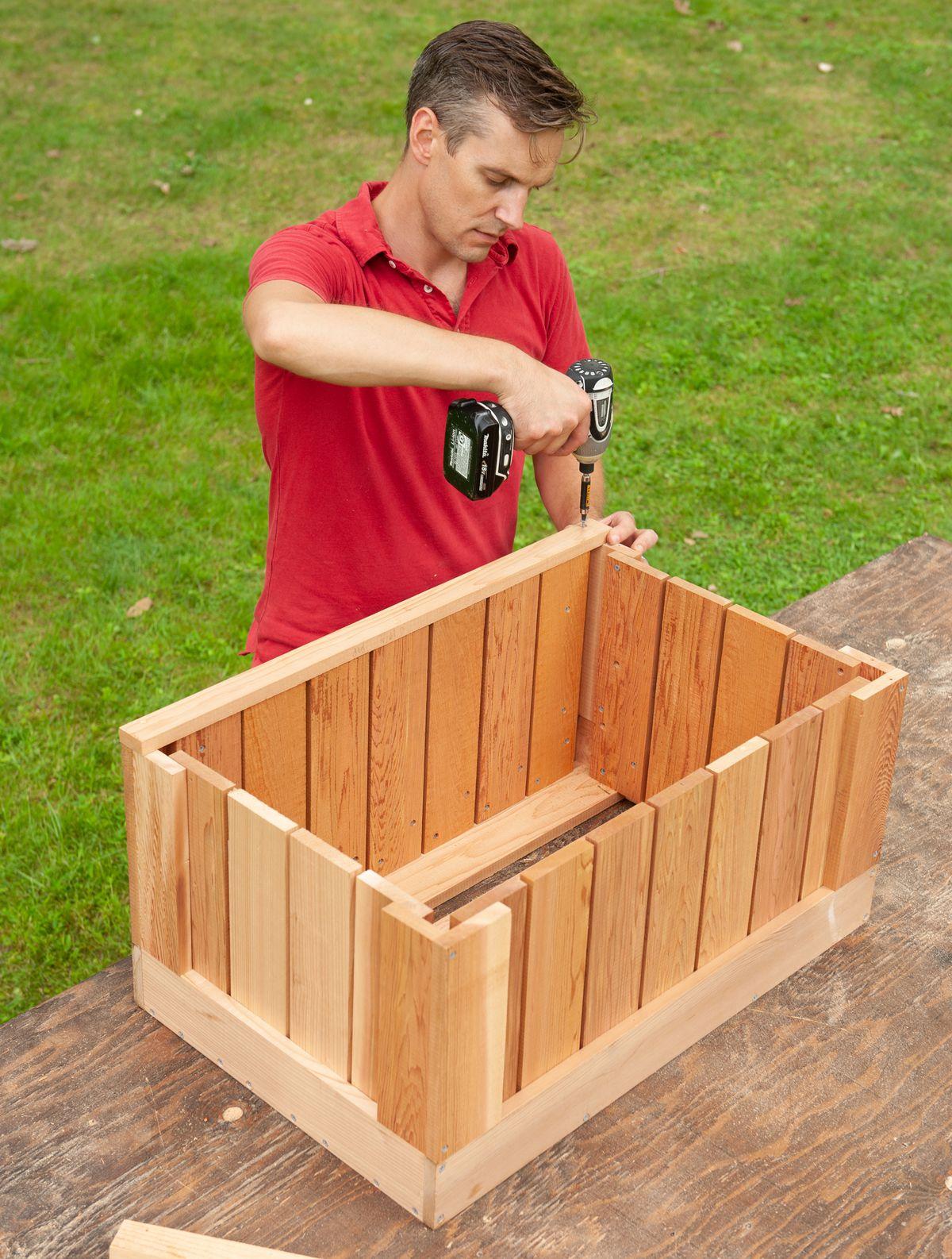 Man Installs Cap For Box Of Cedar Ice Chest