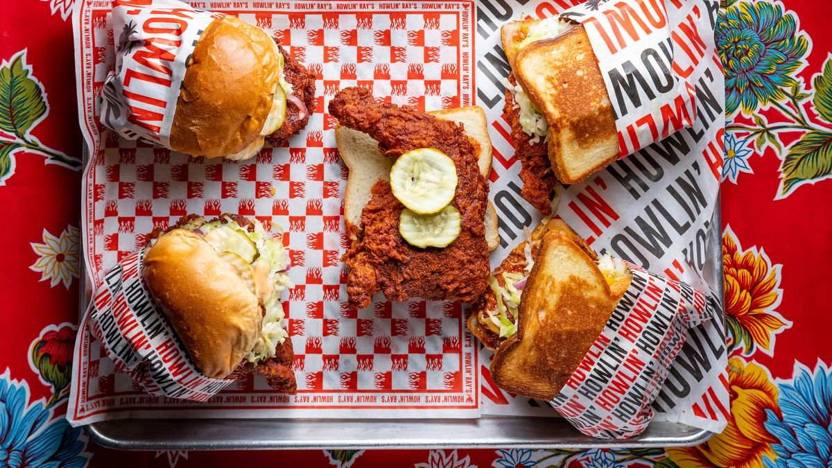 A tray of hot chicken shown from above with checkered paper beneath.