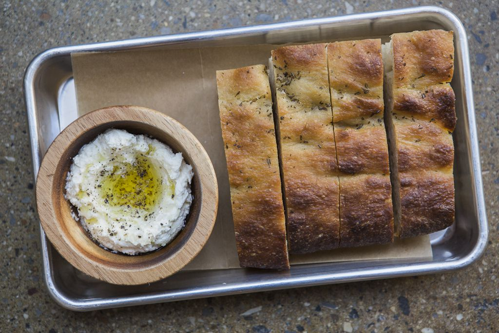 A metal tray holding thick slices of bread next to a wooden bowl of ricotta topped with olive oil