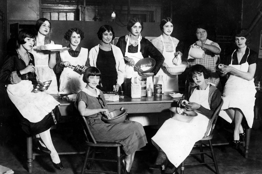 a vintage photograph of women in chairs learning to cook.