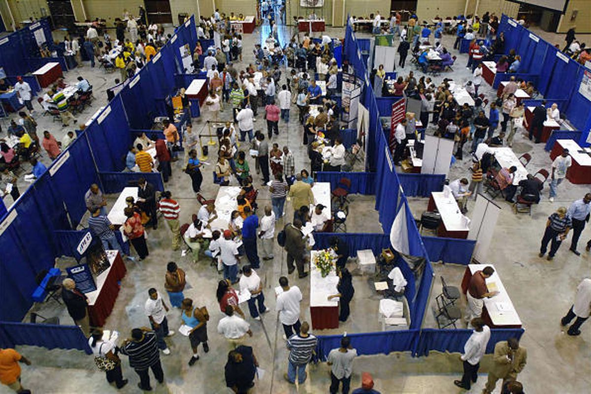 Job seekers attend a job fair in Vicksburg, Miss. The number of newly laid off workers filing jobless claims has fallen.