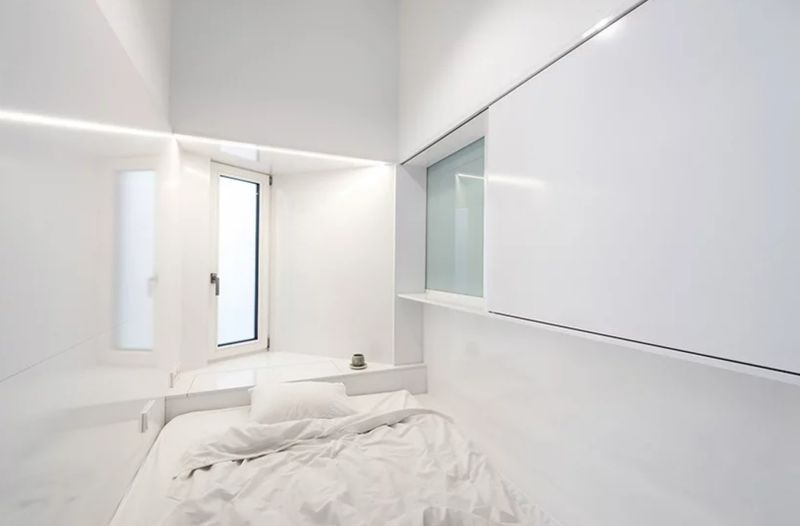 Bedroom nook with white walls and white bed